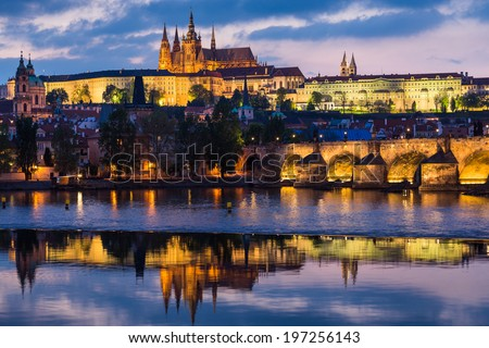 Prague Castle and Charles Bridge at sunset with reflection on Vltava river - stock photo
