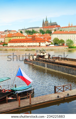 Prague castle and St. Vitus cathedral above Vltava river with Czech flag - stock photo