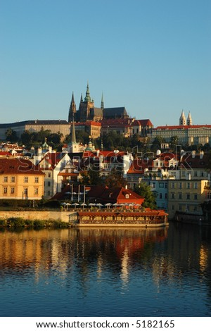 Prague Castle and St. Vitus Cathedral in the early morning sunlight, with reflections on the Vltava river - stock photo