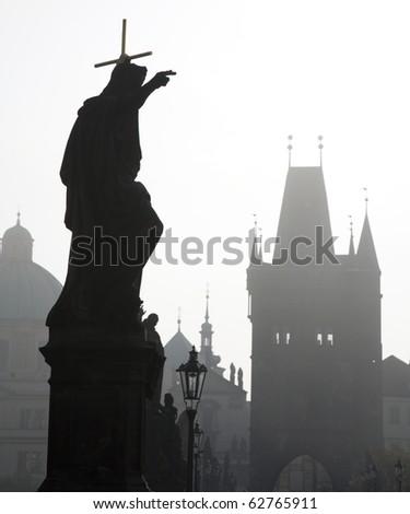 Prague - Charles bridge in the morning fog - st. John the Baptist - stock photo