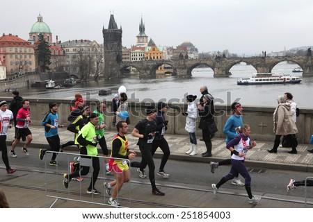 PRAGUE, CZECH REPUBLIC - APRIL 6, 2013: Athletes run over the Manes Bridge on the Vltava River during a marathon run in Prague, Czech Republic. The Charles Bridge is seen in the background. - stock photo