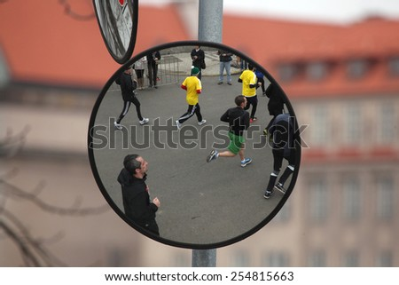PRAGUE, CZECH REPUBLIC - APRIL 6, 2013: Convex mirror with the reflection of athletes running the Prague international marathon in Prague, Czech Republic. - stock photo