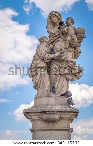PRAGUE, CZECH REPUBLIC - CIRCA JULY 2014 - An old baroque statue of St Anne on the Charles' bridge in Prague, with pigeons - stock photo