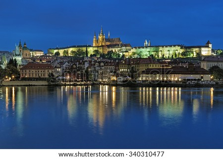 Prague, Czech Republic. Evening view of the Prague Castle with St. Vitus Cathedral and Mala Strana district with St. Nicholas Church and Mala Strana Bridge Towers from the shore of Vltava river. - stock photo