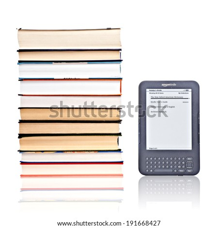 PRAGUE, CZECH REPUBLIC - FEBRUARY 5, 2011: Studio shot of 3rd generation reading device Amazon Kindle in comparison of pile of books. - stock photo