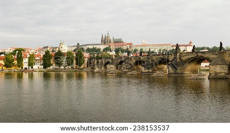 PRAGUE, CZECH REPUBLIC - JULY 1, 2007: An unidentified fisherman on the Vltava River in Prague floats in front of a panorama view of the Hradcany castle and the Charles Bridge. - stock photo