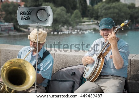 Prague, Czech Republic - June 5, 2016: Bridge Band Praha - two older street musicians, playing their banjo and tuba musical instruments on the famous Charles Bridge built in 1357 - vintage filter - stock photo