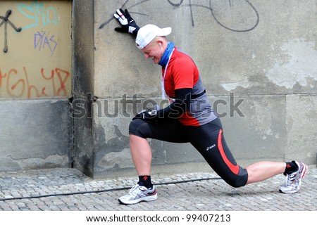 PRAGUE, CZECH REPUBLIC - MARCH 30: Unidentified runner stretches after finishing the Prague Hervis Half  Marathon, March 30, 2012 in Prague, Czech republic. - stock photo