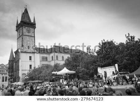 PRAGUE, CZECH REPUBLIC - MAY 3, 2015: Audience waiting for next finishing runners of the Volkswagen Prague Marathon at the Old Town Square, the famous sightseeing place in Prague - black and white - stock photo