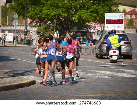 PRAGUE, CZECH REPUBLIC - MAY 3, 2015: Group of female runners of the Volkswagen Prague Marathon 2015 running behind an accompanying motorcycle on circa 33 km of the race - stock photo
