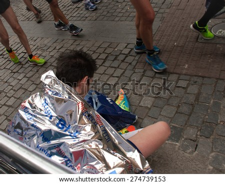 PRAGUE, CZECH REPUBLIC - MAY 3, 2015: Runners who have just finished the Volkswagen Prague Marathon walk from the finish of the marathon in the Old Town Square, the famous place in Prague - stock photo