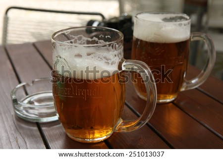 PRAGUE, CZECH REPUBLIC - MAY 13, 2014: Two mugs of traditional Czech beer Pilsner Urquell seen in a pub in Prague, Czech Republic. - stock photo