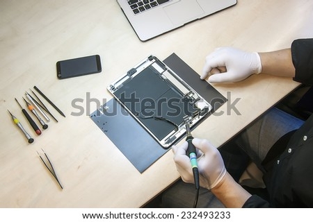 Prague, Czech Republic - NOVEMBER 21, 2014: Photo of the repair process of an iPad Air and iPhone 4. IPad Air and iPhone 4 are produced by Apple Computer, Inc..  - stock photo