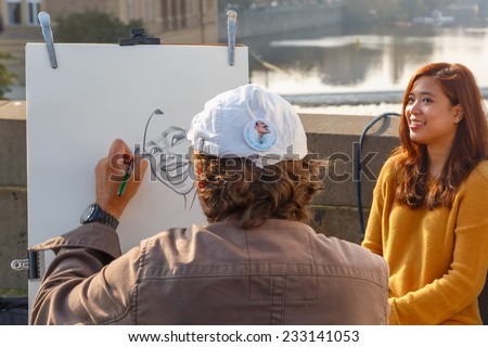 Prague, Czech Republic - October 6, 2014: Street artist paints a portrait-caricature of a beautiful girl on the Charles Bridge. Shallow depth of field, focus on the portrait. - stock photo
