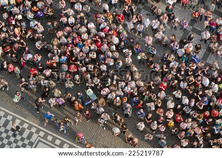 PRAGUE, CZECH REPUBLIC - SEPTEMBER 9, 2014: Aerial Top View of Large group of tourists at Prague central square looking up to Old Town Hall tower. - stock photo