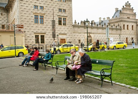 PRAGUE - MAY 16: Couple of elderly tourists sit on the bench and read a guidebook about old city on May 16, 2014 in Czech Republic. Prague receives more than 4.4 million visitors annually  - stock photo