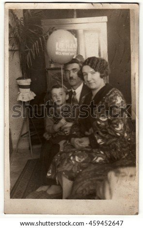 PRAHA (PRAGUE), THE CZECHOSLOVAK REPUBLIC - MARCH 15, 1931: Vintage photo shows family in the living room. Boy holds air-ball (inflatable ball). Retro black & white photography. - stock photo