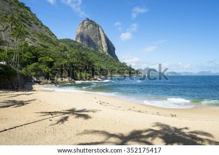 Praia Vermelha Red Beach quiet afternoon with view of Sugarloaf Mountain Pao de Acucar and palm tree shadows Rio de Janeiro Brazil - stock photo