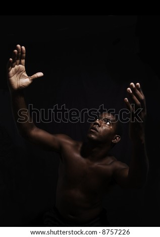 Praise - afromerican man with open arms raised towards the sky - isolated over black - stock photo