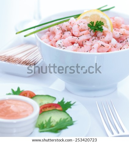 Prawn cocktail in contemporary white bowl displayed with marie rose sauce, side salad and glass of white wine - stock photo