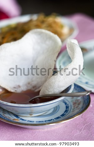 Prawn crackers also know as Dragons Clouds with sweet and sour sauce- Chinese appetizer - stock photo
