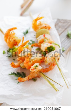 Prawn or shrimp kebab appetizer with grilled pink prawn on skewers with lemon and fresh herbs for a delicious start to a meal - stock photo