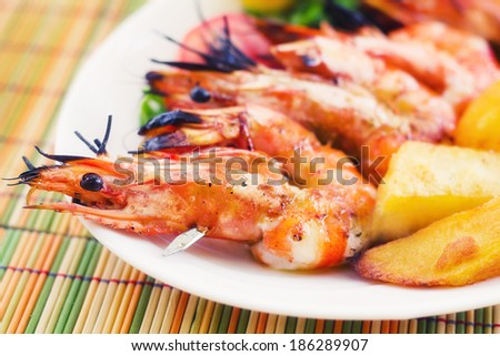 Prawn skewer with a side of baked potatoes (selective focus)  - stock photo
