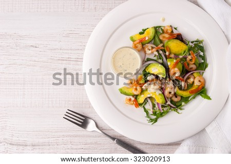 Prawns and avocado salad on the white plate with fork - stock photo