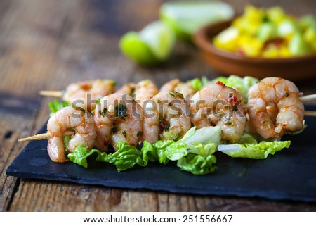 Prawns on skewer with mango salsa in the background - stock photo