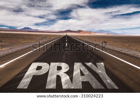 Pray written on desert road - stock photo