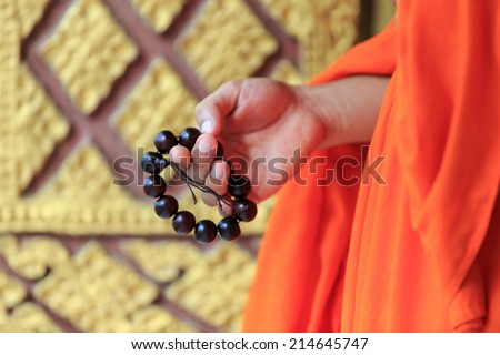 prayer beads in monk's hand, Laos - stock photo