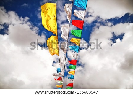 Prayer flags blue sky white clouds sunny day at Mount Everest Base Camp in Tibet China - stock photo
