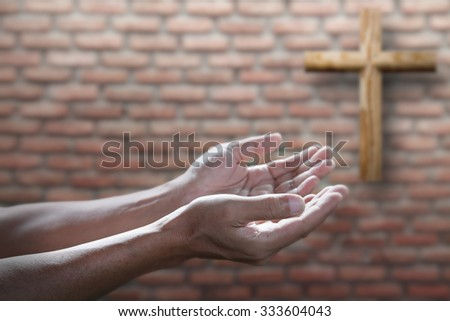 prayer hands and Christian wood cross on old brick wall religion concept - stock photo