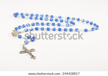Prayer rosary isolated on the bright background - stock photo