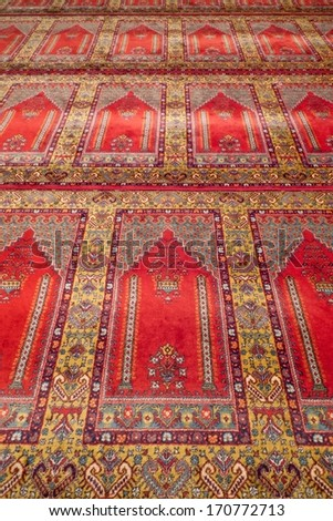 Prayer Rug. Red carpet in a historical Ottoman mosque in Turkey. - stock photo