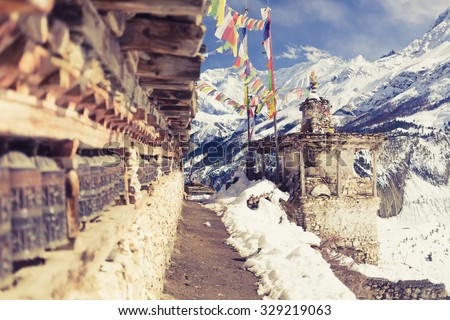 Prayer wheels in high Himalaya Mountains, Nepal village. Focus on the stupa and prayers flags. Annapurna Two range region in Nepal, located at Annapurna Circuit Trekking Hiking Trail - stock photo