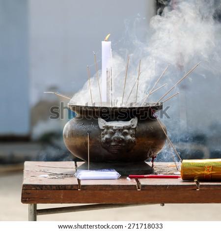 Prayers burning incense sticks on a temple fire. - stock photo