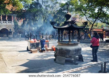Praying at the Buddhist temple, Po Lin Monastery in Hong Kong. Hong Kong is popular tourist destination of Asia. - stock photo