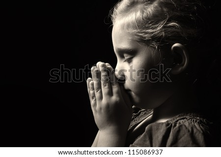 Praying child. MANY OTHER PHOTOS FROM THIS SERIES IN MY PORTFOLIO. - stock photo