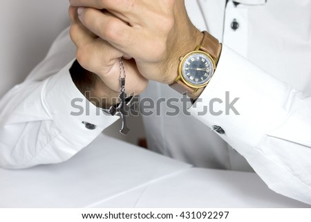 Praying hands holding a rosary - stock photo