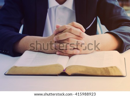 praying hands of the man over the  holy bible on white table, Vintage color effected - stock photo