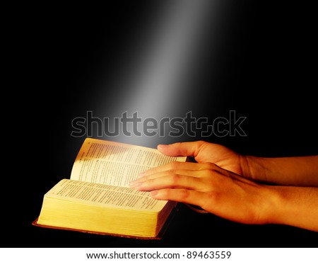 Praying hands on open bible - stock photo