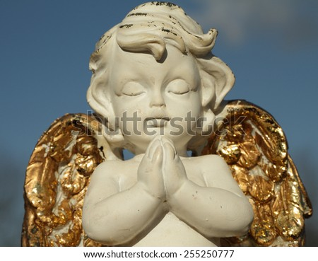 praying little angel figure with golden wings isolated on sky  - stock photo
