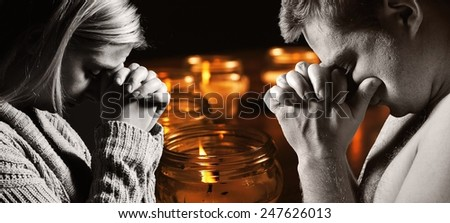 Praying man and woman with candles on background. MANY OTHER PHOTOS FROM THIS SERIES IN MY PORTFOLIO. - stock photo
