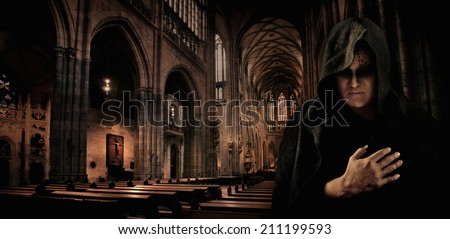 Praying monk in the dark Sanctus Vitus catholic church. - stock photo