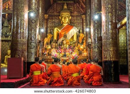 Praying Monks at Wat Xieng Thong luang prabang Laos. - stock photo
