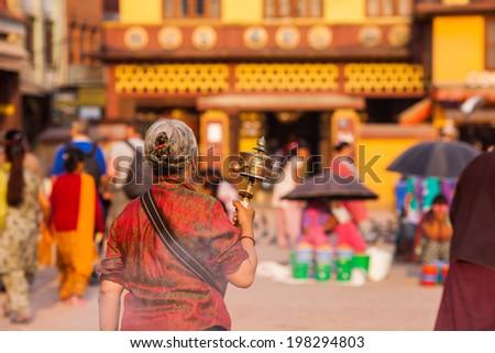 Praying woman at Bodhnath stupa in Kathmandu, Nepal. - stock photo