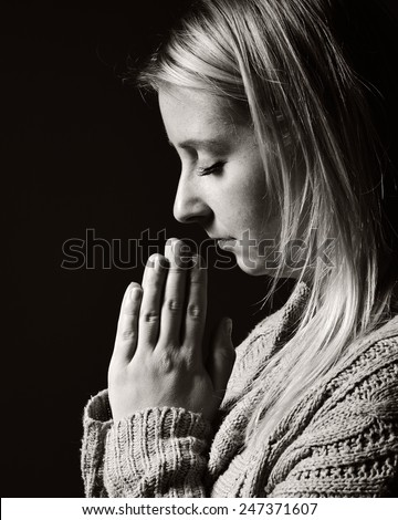 Praying woman. MANY OTHER PHOTOS FROM THIS SERIES IN MY PORTFOLIO. - stock photo