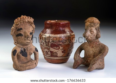 Pre Columbian warriors and pottery made from 600AD to 100BC.  Mayan god painted on small pottery. - stock photo