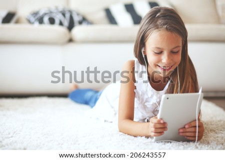 Pre teen girl playing on tablet pc laying down on a white carpet at home - stock photo